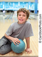 smiling happy boy sits on floor with blue ball in bowling...