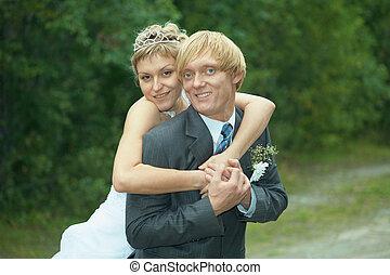 Smiling happy bride embraces groom - The smiling happy bride...