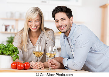 Smiling happy couple drinking wine in the kitchen