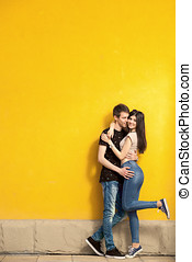 Smiling happy couple on yellow wall