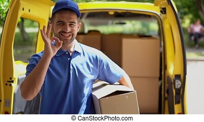 Smiling happy courier man in front of open van doors delivers package and shows ok sign
