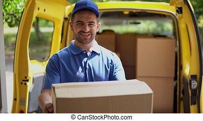 Smiling happy courier man in front of open van doors delivers package