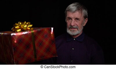 Smiling happy elderly man with a present gift box on black background