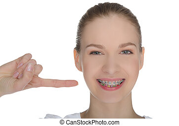 Smiling happy girl indicates braces on teeth isolated on white