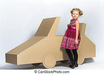 Smiling happy girl near cardboard car. full length female portrait