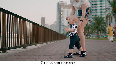 Smiling happy laughing baby takes first steps in summer on the waterfront with mom pointing her finger