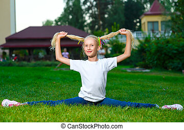 smiling happy little girl doing split and holding itself for pigtails