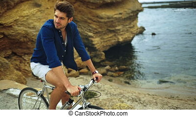 Smiling happy model posing with a bicycle on the stony beach.