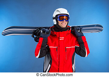 Smiling happy sportsman holding snowboard over shoulder. Looking away and standing isolated over blue background