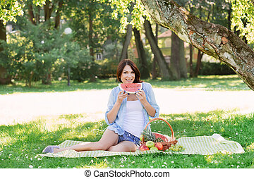 Smiling happy woman eating a watermelon in the park