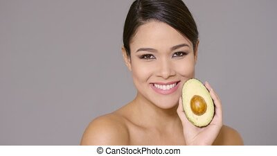Smiling happy woman holding a ripe avocado pear