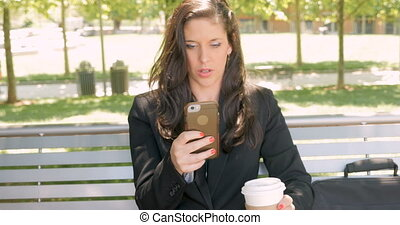 Smiling happy woman on her smart phone while drinking coffee on lunch break