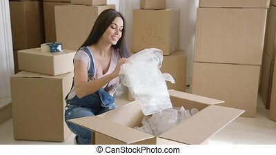 Smiling happy woman packing up her home in preparation for...