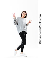 Smiling happy woman showing peace gesture with two hands