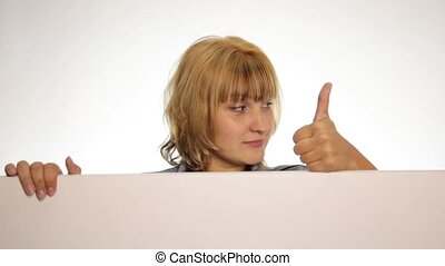 Smiling happy woman standing behind and leaning on a white blank billboard or placard, expresses different emotions and shows thumb to the top. over white background