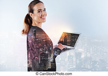 Smiling happy woman with ponytail holding a laptop