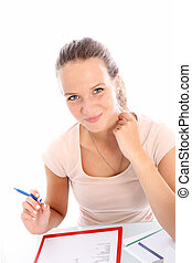 Smiling beautiful hardworking young female student sitting at her desk studying and making notes