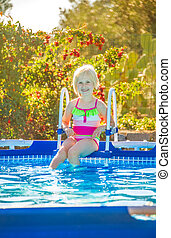 smiling healthy girl sitting in swimming pool