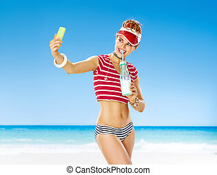 smiling healthy woman in red sun visor on seashore with ...