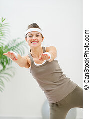 Smiling healthy woman making gymnastics exercise