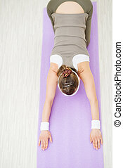 Smiling healthy woman on fitness mat doing yoga