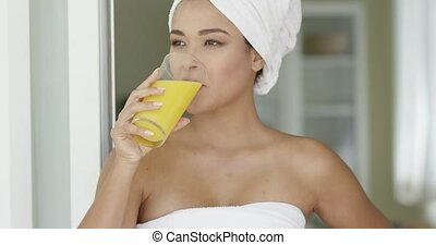 Smiling healthy young woman drinking orange juice