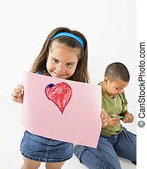 Smiling hispanic girl holding drawing.
