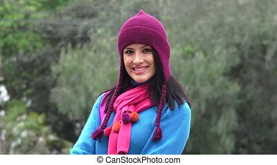 Smiling Hispanic Woman Wearing Sweater And Knit Hat Cold...