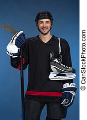 Smiling hockey player looking at camera with skates over shoulder. Isolated on blue