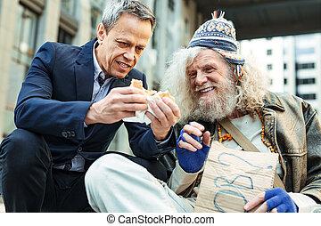 Smiling homeless elderly man eating burger from stranger
