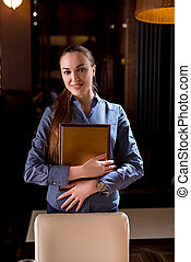 Smiling hostess of fashionable restaurant posing