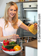 Smiling housewife preparing pasta