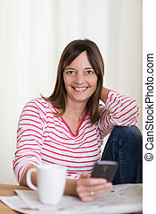 Smiling housewife relaxing over morning coffee sitting at...