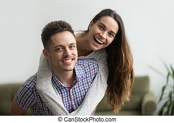 Smiling husband piggybacking cheerful wife at home, happy couple