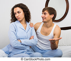 Smiling husband trying to reconcile with wife