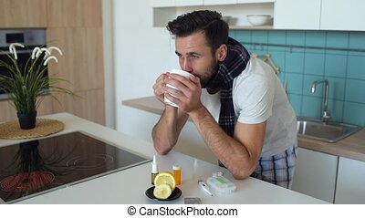Smiling ill gentleman drinking tea and looking into camera -...
