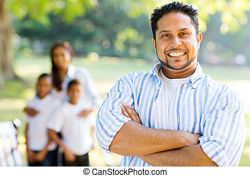 indian father with arms crossed in front of family