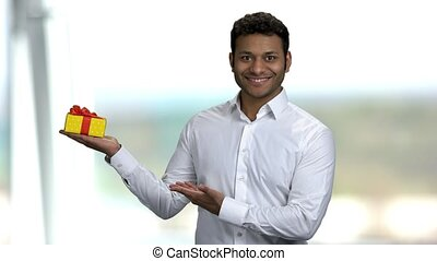 Smiling Indian guy presenting gift box. Handsome businessman...