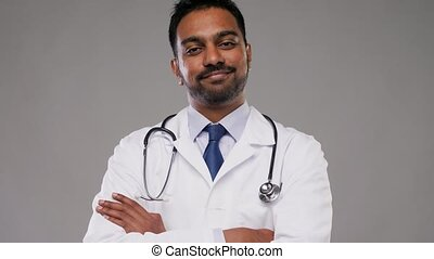 smiling indian male doctor with stethoscope - medicine,...