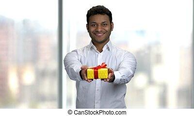 Smiling Indian man giving gift box.