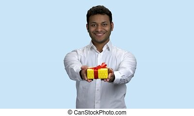 Smiling Indian man handing gift box. Young handsome businessman offering present box on color background. Birthday celebration concept.