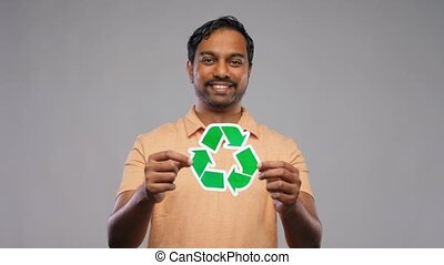 eco living, environment and sustainability concept - happy smiling young indian man in polo t-shirt holding green recycling sign over grey background