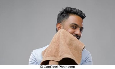 smiling indian man with towel over grey background -...