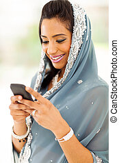 smiling indian woman reading emails on smart phone - smiling...