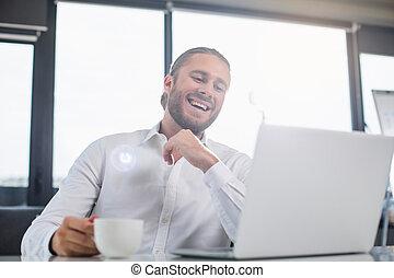 Smiling intelligent businessman with mug of beverage