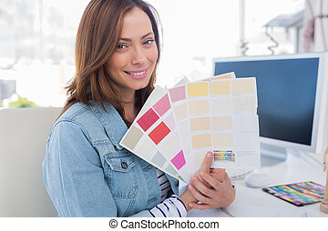 Smiling interior designer holding up colour samples and...