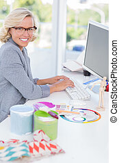 Smiling interior designer working on her computer
