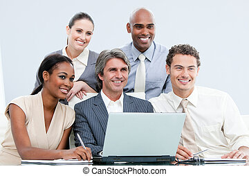 Smiling internationnal businessteam working with at the laptop