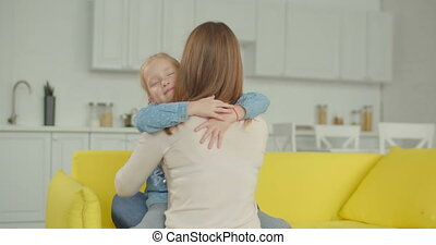 Smiling joyful little girl embracing mother happily -...
