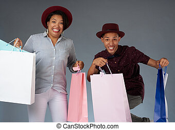 Smiling jumping young couple with shopping bags